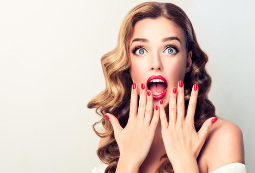 Kvinde med rød neglelak og rød læbestift