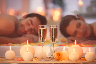Par får romantisk massage med levende lys og champagne